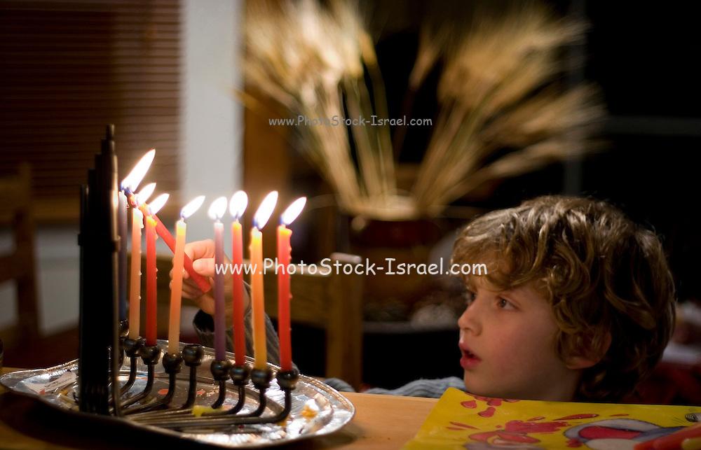 young boy Lighting the Chanukia