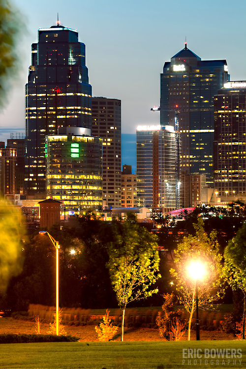 Kansas City downtown skyline, vertical photo at dusk with the new One Light Tower residential apartment high rise nearing completion in center.