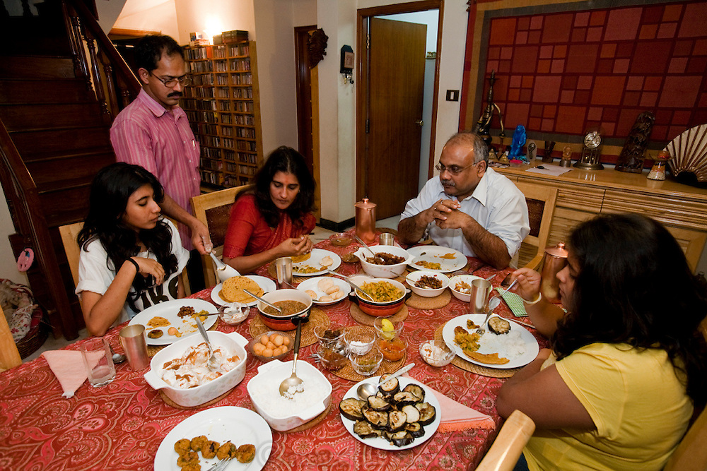 Millie Mitra (center), an education consultant and homeopathy devotee, enjoys dinner with her family at home in Benson Town, Bangalore, India. (Millie Mitra is featured in the book What I Eat: Around the World in 80 Diets.) Millie's quest for health includes yoga, a vegan diet, a daily glassful and topical applications of her own urine. She has a thirst for alternative medicine and homeopathic healing, as well as a deep interest in how her diet affects her body. She has practiced Shivambu (sometimes spelled Sivambu), which is the drinking of one's own first morning urine (200 cc in her practice) as a curative and preventative measure, for over 15 years. Millie applies urine to her skin as well, for the same reasons. Her husband Abhik has tried Shivambu and she helped her children to practice it when they were young, but currently only Millie practices urine therapy in her family. MODEL RELEASED.