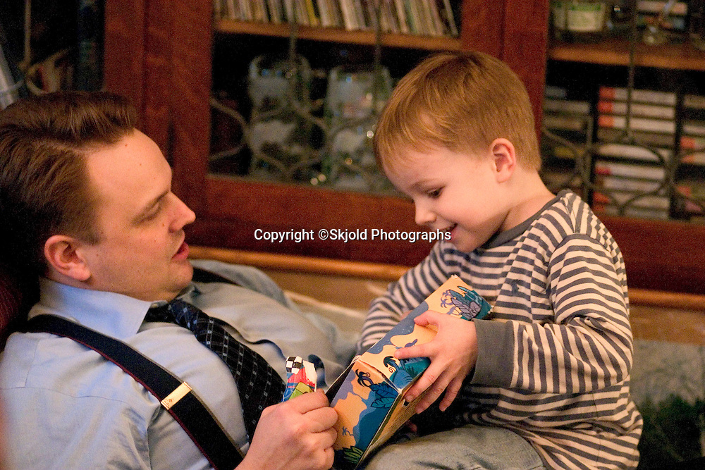 Son enthusiastically showing dad age 4 and 34 his wrapped birthday gift.  St Paul Minnesota USA