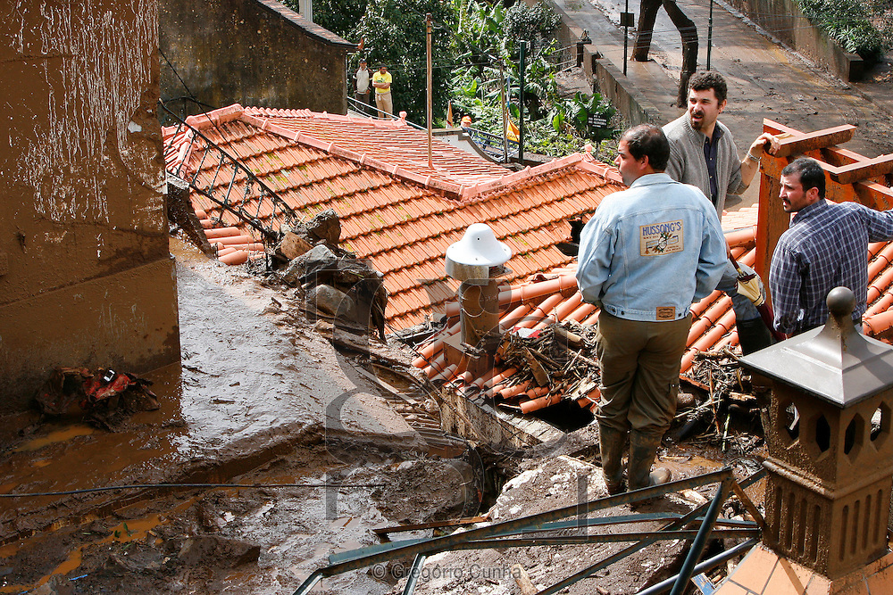 Portugal, FUNCHAL : Villagers clear the mud from their doorstep in Funchal, Madeira Island, on February 22, 2010. Residents fled their homes for fear of new mudslides on the tourist island of Madeira as Portugal decreed three days of mourning for the 42 people killed in weekend flash floods. .Photo Gregorio Cunha