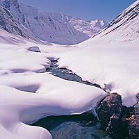 GREAT HIMALAYA RANGE, KASHMIR, INDIA. Snowbound stream flows through Warwan Valley.