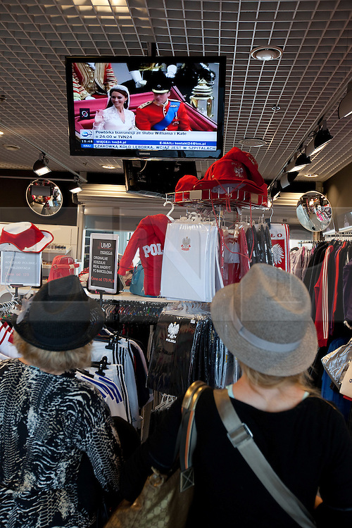 © licensed to London News Pictures. London, UK 24/04/2011. The Royal Wedding of HRH Prince William to Kate Middleton. In Poland the event is shown on screens in shops. Passers by watch through the door. Please see special instructions for usage rates. Photo credit should read Joel Goodman/LNP.