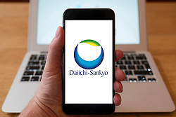 Using iPhone smartphone to display logo of Daiichi-Sankyo; a global pharmaceutical company