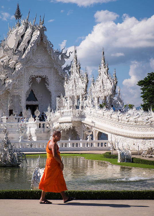 """A monk walks past Wat Rong Khun, the """"white temple"""" outside of Chiang Rai in Northern Thailand."""