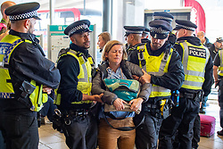 © Licensed to London News Pictures. 10/10/2019. London, UK. An Extinction Rebellion protester is removed by police as protesters block the entrance to London City Airport. Protesters arrived via the Docklands Light Rail and proceeded to conduct a sit-in to block the entrance from the train station to the airport. Photo credit: Peter Manning/LNP