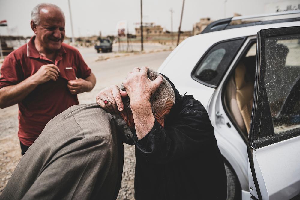 Qaraqosh, Iraq - May 20, 2017: Seventy-eight-year-old Imam Bhnam greets Bashar Azoo Boutros Alkhashanna in the predominately Christian town of Qaraqosh. Her son, Mazin, stands in the background.