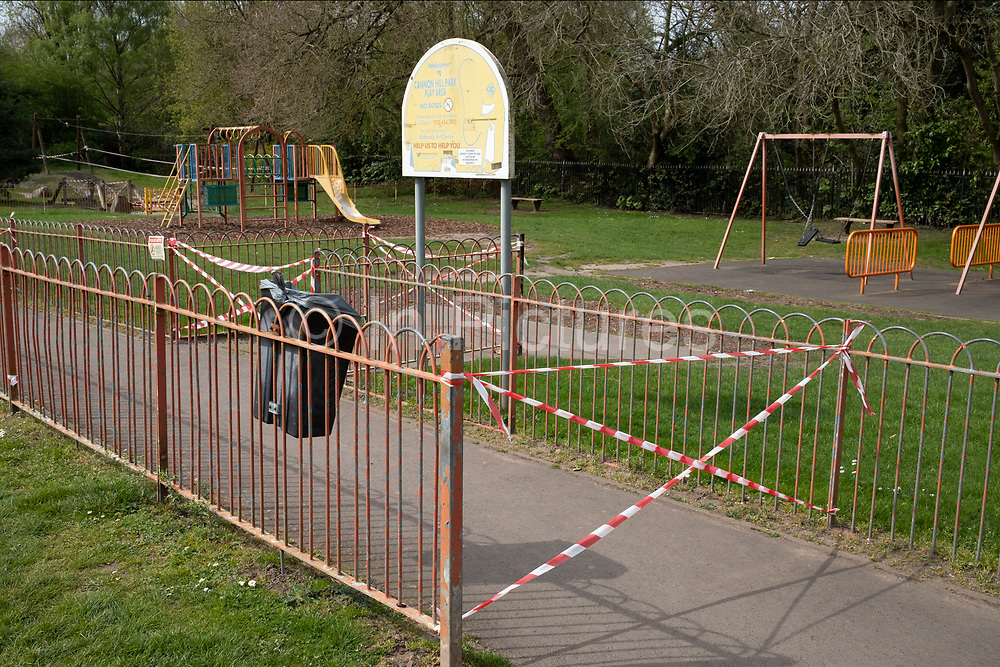 Childrens playground is cordoned off to prevent children getting too close while playing in Canon Hill Park as Coronavirus is felt on a local level on 12th April 2020 in Birmingham, England, United Kingdom. People here, in what is normally an incredibly busy urban park are mainly abiding the stay at home message, and those out exercising are doing so with care. Coronavirus or Covid-19 is a new respiratory illness that has not previously been seen in humans. While much or Europe has been placed into lockdown, the UK government has announced more stringent rules as part of their long term strategy, and in particular social distancing.