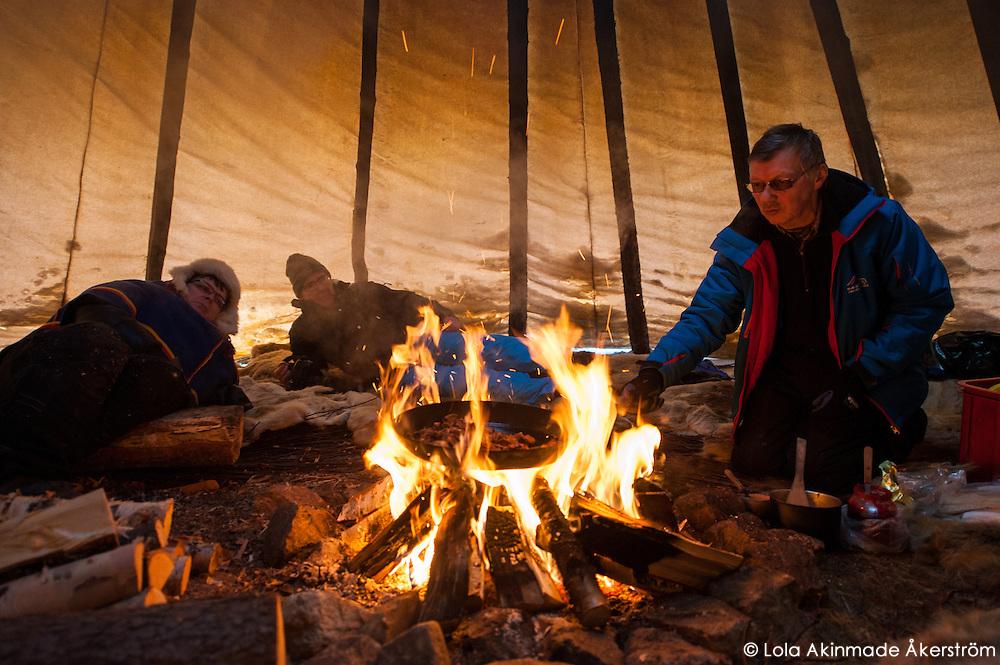 Per-Anders Nutti cooking souvas (smoked reindeer meat) inside a tentipi (lávvu)