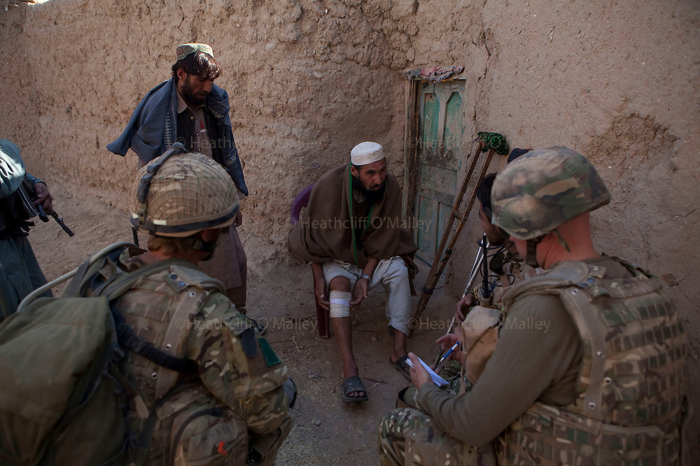 Mcc0027461 . Daily Telegraph..Mullah Abdullahjan shows the wound he received recently possibly inflicted by ISAF forces on a previous operation...Paratroopers from A coy, 3 Para under the command of Lt Jamie Macdonald on patrol south of their base CP Qudtrat in the northern Nad e Ali district of Helmand. ..Helmand 2 December 2010