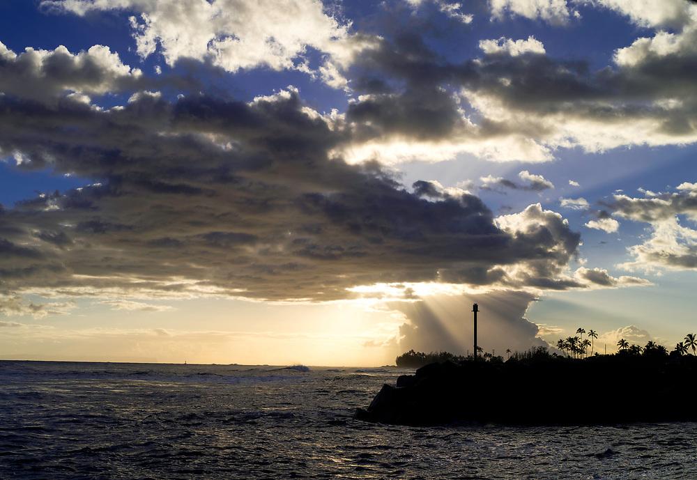 Sunset through the clouds at Kekaha Harbor, on the southwest side of Kauai, Hawaii, USA.
