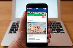 Using iPhone smartphone to display very expensive house for sale in London on property website Zoopla