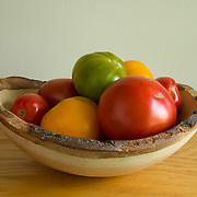 Heirloom tomatoes, in a hand-carved wooden bowl, just picked.