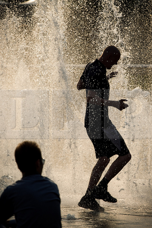 © Licensed to London News Pictures . 05/07/2013 . Manchester , UK . As the sun sets , a man , silhouetted against the backlit fountains in Manchester City Centre 's Piccadilly Gardens , cools off by leaping through the jets of water . People enjoy the heat and sunshine in Manchester City Centre . Photo credit : Joel Goodman/LNP