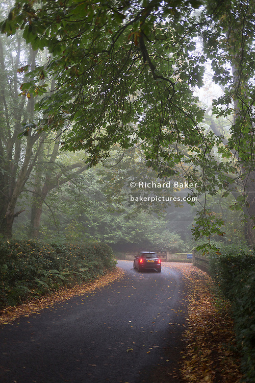 A car brakes to corner a tight bend on a rural Northumbrian road, early on an autumnal morning, on 26th September 2017, in Eshott, Northumberland, England.