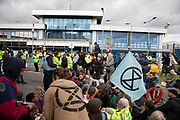 Extinction Rebellion disruption outside City Airport on 10th October 2019 in London, England, United Kingdom. The protest is against the climate and pollution impact of the government's plans for airport expansion which will potentially double the amount of flights coming from City Airport. Extinction Rebellion is a climate change group started in 2018 and has gained a huge following of people committed to peaceful protests. These protests are highlighting that the government is not doing enough to avoid catastrophic climate change and to demand the government take radical action to save the planet.
