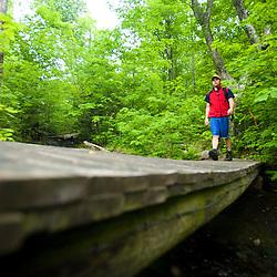 A hiker crossing a stream on Monadnock Mountain in Lemington, Vermont.  The Northeast Kingdom.