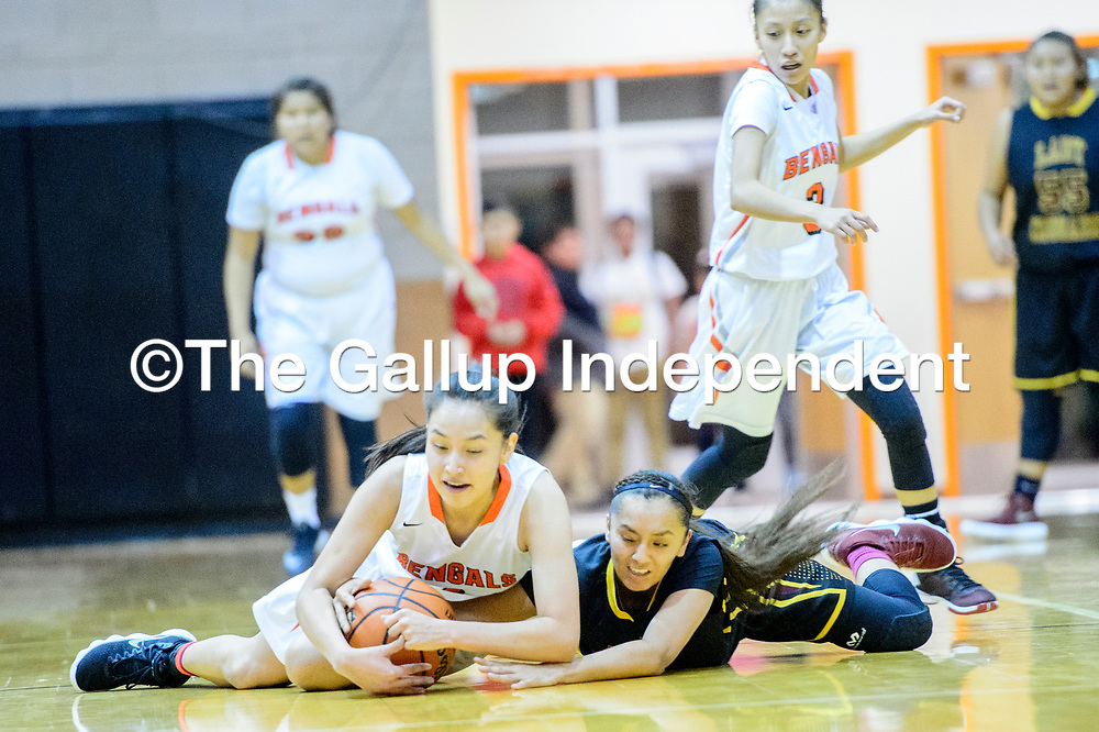 Gallup Bengal Ashley Antone (1), left, andTohatchi Cougar Kalian Mitchell (5) tie up for a loose ball at Gallup High School Tuesday.
