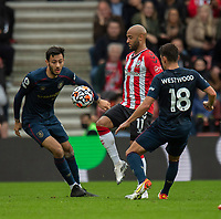 Southampton's Nathan Redmond (centre) vies for possession with Burnley's Dwight McNeil (left) and Ashley Westwood (right) <br /> <br /> Photographer David Horton/CameraSport<br /> <br /> The Premier League - Southampton v Burnley - Saturday 23rd October 2021 - St Mary's Stadium - Southampton<br /> <br /> World Copyright © 2020 CameraSport. All rights reserved. 43 Linden Ave. Countesthorpe. Leicester. England. LE8 5PG - Tel: +44 (0) 116 277 4147 - admin@camerasport.com - www.camerasport.com