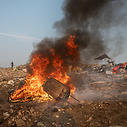Burning luggage to collects metal in it. Located next to a lake, a visit to one of the main garbage dump in Kolkata. With 15 millions population in 2019 and growing, the city of Calcutta is a typical case of expansion through uncontrolled urbanization.A woman who burns luggage to collects metal in it. Located next to a lake, a visit to one of the main garbage dump in Kolkata. With 15 millions population in 2019 and growing, the city of Calcutta is a typical case of expansion through uncontrolled urbanization.