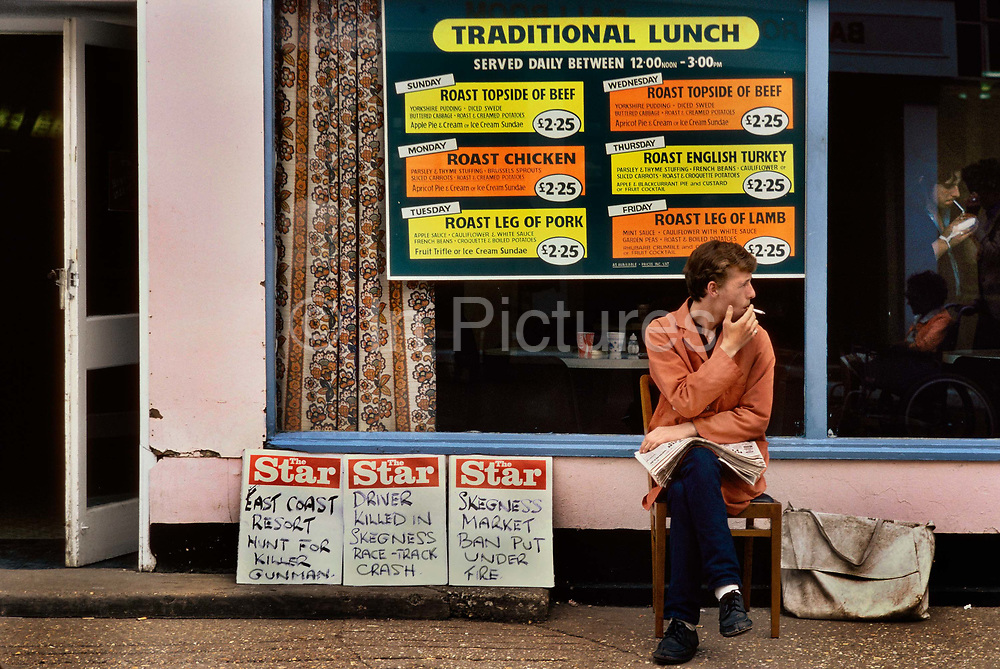 Man selling the local paper in front of the traditional dining room in Butlins Holiday camp, Skegness. Butlins Skegness is a holiday camp located in Ingoldmells near Skegness in Lincolnshire. Sir William Butlin conceived of its creation based on his experiences at a Canadian summer camp in his youth and by observation of the actions of other holiday accommodation providers, both in seaside resort lodging houses and in earlier smaller holiday campsThe camp began opened in 1936, when it quickly proved to be a success with a need for expansion. The camp included dining and recreation facilities, such as dance halls and sports fields. Over the past 75 years the camp has seen continuous use and development, in the mid-1980s and again in the late 1990s being subject to substantial investment and redevelopment. In the late 1990s the site was re-branded as a holiday resort, and remains open today as one of three remaining Butlins resorts.