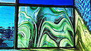 Sunlit colorful blue and green stained glass window, with textural wavy elements