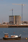 Tower cranes and construction sites above fishing boats on the River Medway near Rochester in Kent, England UK. April 16th 2008
