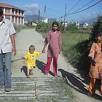 Asia, Nepal, Kathmandu. Teenage friends walking with toddler in Kitipur.