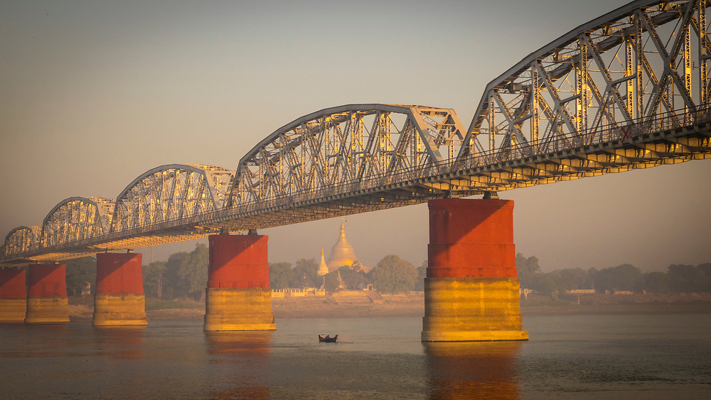 The Ava, or Sagaing, bridge on the Irriwaddy river at sunrise, with one of the many temples in the background. Built by the British in 1934. The bridge was destroyed by the retreating British Army during World War II and was rebuilt in 1954 after Burmese independence