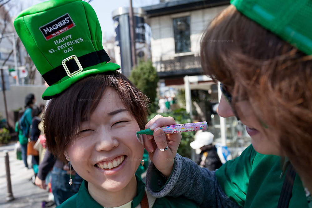 """A Japanese woman gets here face painted at the 27th Saint .Patrick's Day Parade in Omotesando, Tokyo, Japan. Sunday March 17th 2019. Started in 1992 by the Irish Network, Japan, and supported by the Embassy of Ireland,; the parade, along with the """"I Love Ireland Festival"""" held nearby is Asia's  largest Irish event."""