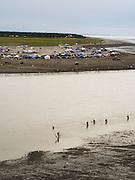 Fishers wade into the mouth of the Kenai River to net salmon. Kenai, Alaska.