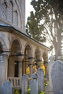 Afternoon sunlight streams through trees and Ottoman-era headstones outside the tomb of Suleiman the Magnificent, located at the Süleymaniye Mosque in Istanbul, Turkey. The mosque was built between 1550 and 1557.