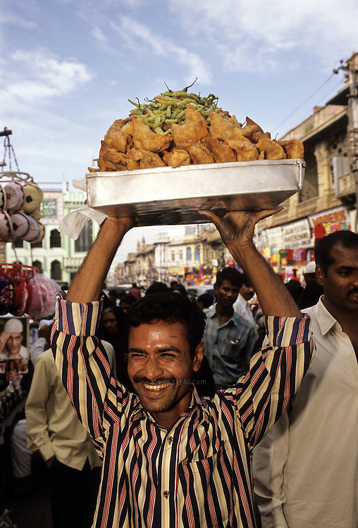 A Samosa vendor on the streets of Hyderabad (AP) carries the tray over his head to protect it from the crowd..A samosa is a common snack India. It generally consists of a fried triangular-/pyramid-shaped pastry shell with a savory potato, onion and pea stuffing, but other stuffings like minced meat and fish are often used. The size and shape of a samosa, as well as the consistency of the pastry used, can vary considerably. It is spicy and is often eaten with chutney, such as mint, coriander or tamarind. It is often savored with tea or coffee. It can also be prepared as a sweet form, rather than as a savory one. In the city of Hyderabad, India, a smaller version of the samosa with a thicker pastry crust and mince filled center is called a Luqmi.