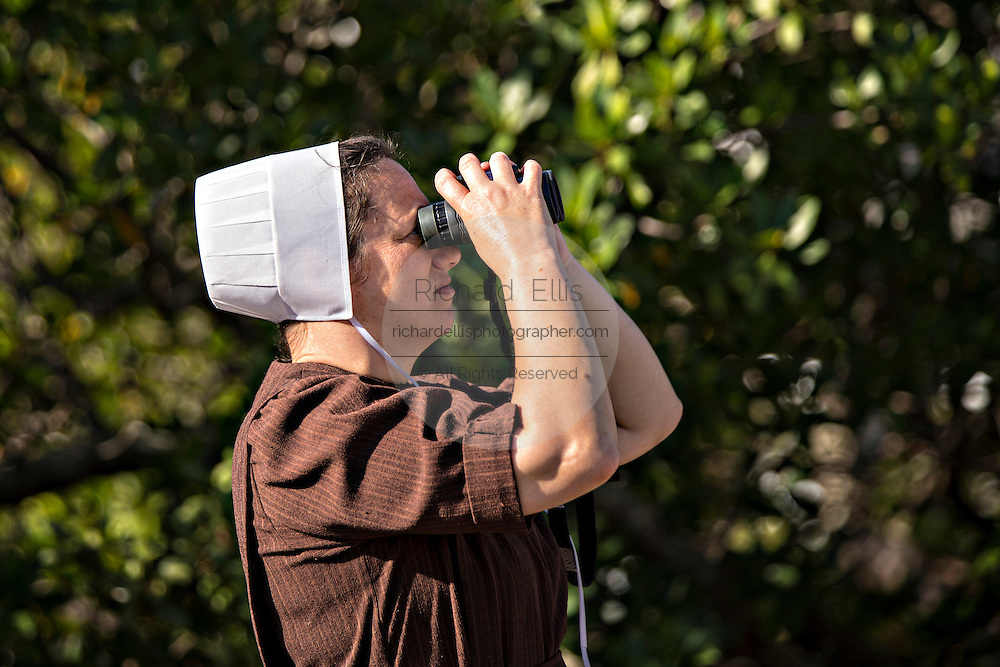 An Amish woman looks though binoculars Sarasota, Florida