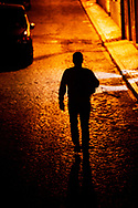 Back view of a man walking alone at night in a cobblestone alley