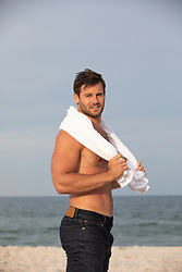 hot man without a shirt holding a towel around his neck at the ocean