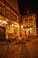 View of the Weinhaus Altes Haus restaurant, outdoor seating, tudor buildings on a cobblestone street. Bacharach, Germany.