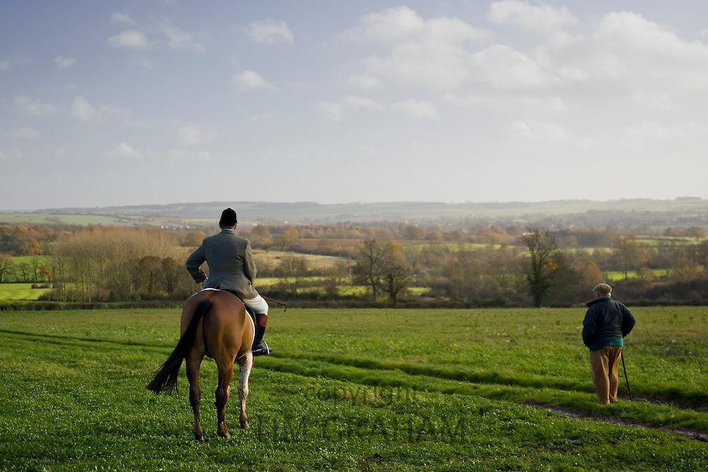 Rider admires far-reaching view with walker, The Cotswolds, Oxfordshire, United Kingdom