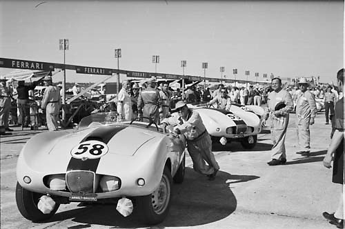 """Stan """"Wacky"""" Arnolt, automaker and driver, stands at right ready to race his Arnolt Bristol no. 58 at Sebring 1955"""