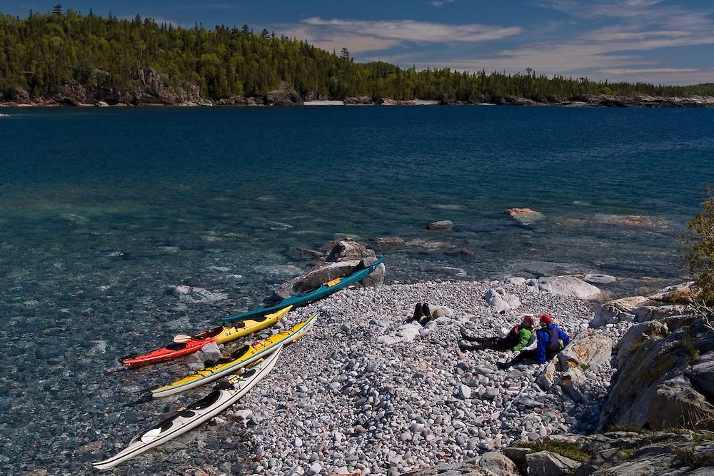 Sea kayakers explore the rugged shoreline of Ryan Point in Lake Superior Provincial Park near Wawa Ontario Canada.