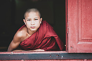 Nyaungshwe, Myanmar - November 4, 2011: A teenage boy and novice monk looks out a window of his monastery in Nyaungshwe, a town on the northern end of Inle Lake in Shan State.