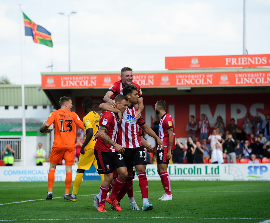 Lincoln City's Tyler Walker, right, celebrates scoring his side's third goal from the penalty spot with team-mates Harry Anderson, left, and Joe Morrell<br /> <br /> Photographer Chris Vaughan/CameraSport<br /> <br /> The EFL Sky Bet League One - Lincoln City v Southend United - Saturday 17th August 2019  - Sincil Bank - Lincoln<br /> <br /> World Copyright © 2019 CameraSport. All rights reserved. 43 Linden Ave. Countesthorpe. Leicester. England. LE8 5PG - Tel: +44 (0) 116 277 4147 - admin@camerasport.com - www.camerasport.com