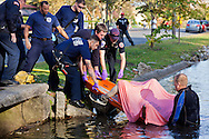 Firefighters remove a body from a lake.