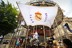 3 June 2017 - UEFA Champions League Final - Juventus v Real Madrid - A Real Madrid fan waves a flag as he rides a carousel - Photo: Marc Atkins / Offside.