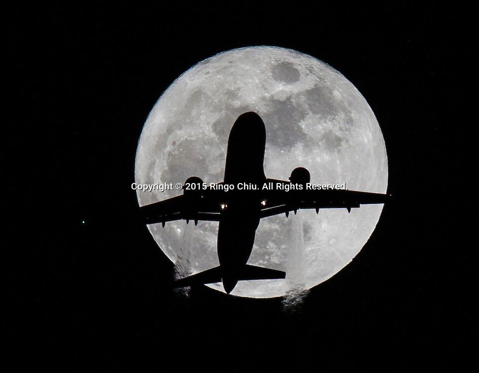 An American Airlines Flight AA1249 passenger airplane approaching Los Angeles International Airport flies past the Full Beaver Moon in Los Angeles, California, on November 25, 2015.(Photo by Ringo Chiu/PHOTOFORMULA.com)<br /> <br /> Usage Notes: This content is intended for editorial use only. For other uses, additional clearances may be required.