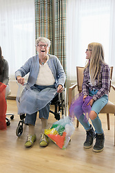 Girls and senior woman doing gentle sports exercise with cloth in rest home