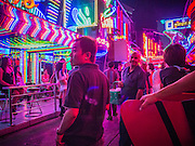 "29 DECEMBER 2012 - BANGKOK, THAILAND:  Tourists on ""Soi Cowboy"" one of the red light districts in Bangkok, Thailand. Soi Cowboy, along with Nana Entertainment District and Patpong, are the districts that first brought Bangkok fame as a sex tourism destination. The areas got their start during the 1960's when American servicemen serving in Vietnam came to Thailand on ""R&R.""     PHOTO BY JACK KURTZ"
