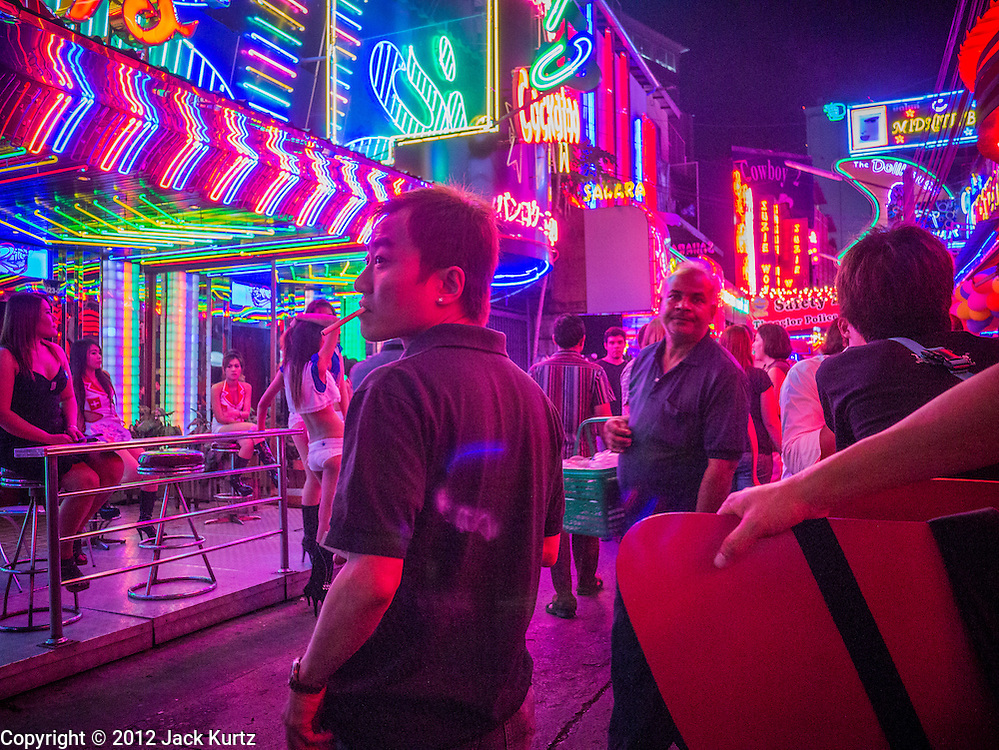 """29 DECEMBER 2012 - BANGKOK, THAILAND:  Tourists on """"Soi Cowboy"""" one of the red light districts in Bangkok, Thailand. Soi Cowboy, along with Nana Entertainment District and Patpong, are the districts that first brought Bangkok fame as a sex tourism destination. The areas got their start during the 1960's when American servicemen serving in Vietnam came to Thailand on """"R&R.""""     PHOTO BY JACK KURTZ"""