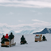 Tourists ride in komatik sleds behind snowmobiles on frozen Eclipse Sound