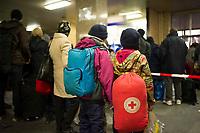 DEU, Deutschland, Germany, Berlin, 29.12.2015: Ankunft von Flüchtlingen im Bahnhof Schönefeld. Eine Familie mit zwei Kindern wartet auf den Bus, der sie in die Flüchtlingsunterkunft bringen wird. Kind mit rotem Rucksack des Griechischen Roten Kreuzes.